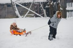 Boy pulls sledges with younger sister Royalty Free Stock Photos