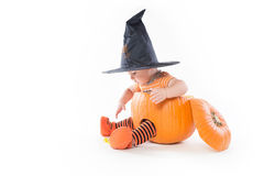 Little boy in a pumpkin in witch hat reaching for candy Stock Images