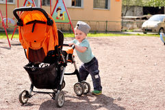 Little boy pushes carriage at playground. In daylight Royalty Free Stock Photos
