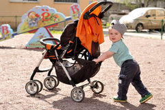 Little boy pushes carriage at playground. In daylight Stock Photos