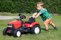 Little boy pushes tractor Stock Photography