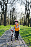 Little boy pushing his bicycle in a park Royalty Free Stock Images