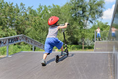Little boy pushing a scooter up a ramp Stock Photos