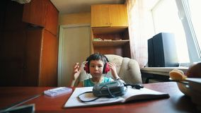 A little boy put on the headphones and turn on the cassette player - russian old interior. Mid shot stock video footage