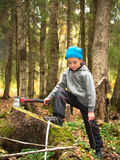 Little boy put his foot on a stump and holding an ax in his hand Stock Photography