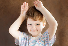 Little boy put his hands to his head Stock Photo