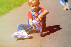 Little boy put on roller skates outdoors Royalty Free Stock Photos