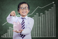 Little boy puts the coin into the piggy bank Stock Photos