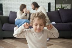 Little boy puts fingers in ears, parents fighting at background Stock Photos