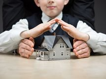 Little boy puts hands as roof over house model Royalty Free Stock Photo