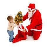 Little boy puts small tree in Santa's bag Stock Photos