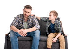 Little boy putting hand on shoulder of father sitting on sofa and looking away Royalty Free Stock Image
