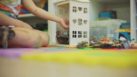 Little Boy Putting Toy Animals into the Toy House. Little Boy Putting Toy Animals into a Toy House. He is Playing on the Floor in Nursery Room. Close-Up Shot stock footage