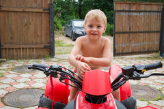 Little boy on a quad bike stands Royalty Free Stock Image