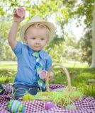 Little Boy que abre los huevos de Pascua afuera en parque Foto de archivo libre de regalías