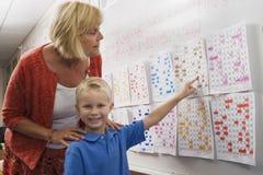 Little Boy que aponta a uma data de calendário para o professor imagens de stock