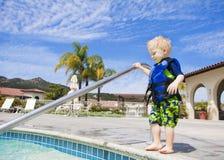 Little Boy que camina prudentemente en piscina al aire libre Imagenes de archivo