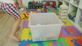Little Boy que coge los juguetes después de jugar en casa almacen de video