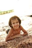 Little Boy que coloca na praia Imagens de Stock Royalty Free