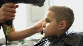 Little Boy que consigue corte de pelo de Barber While Sitting In Chair en la barbería  almacen de metraje de vídeo