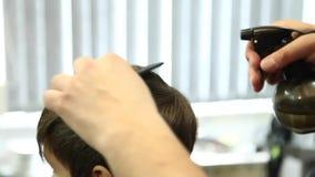 Little Boy que consigue corte de pelo de Barber While Sitting In Chair en la barbería  metrajes