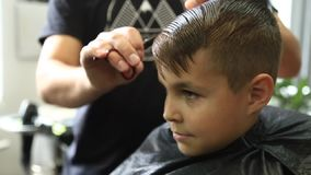 Little Boy que consigue corte de pelo de Barber While Sitting In Chair en la barbería  almacen de video