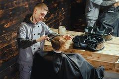 Little Boy que consigue corte de pelo del peluquero Imagen de archivo libre de regalías