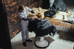 Little Boy que consigue corte de pelo del peluquero Foto de archivo libre de regalías
