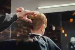Little Boy que consigue corte de pelo del peluquero Fotografía de archivo