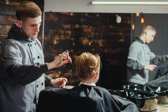 Little Boy que consigue corte de pelo del peluquero Imagenes de archivo