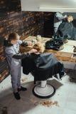 Little Boy que consigue corte de pelo del peluquero Foto de archivo