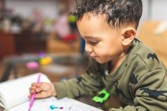 Little Boy que dibuja en un cuaderno foto de archivo