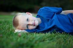Little Boy que encontra-se na grama Foto de Stock Royalty Free