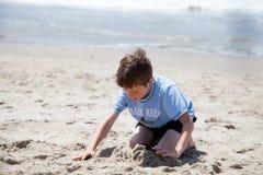 Little Boy que joga com a areia na praia Fotografia de Stock