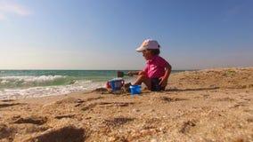 Little Boy que joga com a areia na praia video estoque