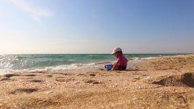 Little Boy que joga com a areia na praia filme