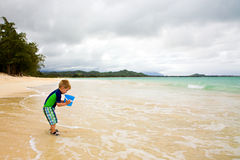 Little Boy que juega con un compartimiento en la playa Fotografía de archivo