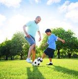 Little Boy que juega a fútbol con su padre Concept Fotos de archivo