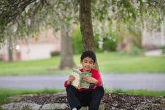 Little Boy que lê um livro debaixo de uma árvore Foto de Stock