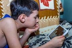 Little Boy que olha a tabuleta digital com expressão da cara imagem de stock