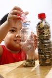 Little Boy que pone el dinero en una botella Imagen de archivo libre de regalías