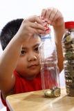 Little Boy que pone el dinero en una botella Fotografía de archivo