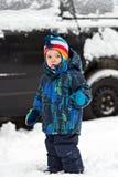 Little Boy que se coloca delante de un coche en la nieve Fotos de archivo libres de regalías