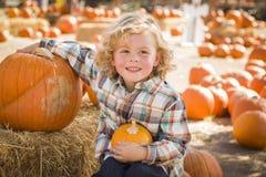 Little Boy que senta e que guarda sua abóbora no remendo da abóbora Fotos de Stock