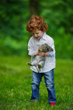 Little boy with rabbit on grass Stock Photography