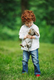 Little boy with rabbit on grass Stock Photo