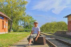 Little boy on a railway station, waiting for the train with vintage suitcase. Traveling, holiday and chilhood concept. Travel ins royalty free stock images