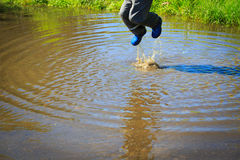 Little boy in rain boots jumping into water puddle Royalty Free Stock Photos