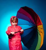 Little boy with rainbow-colored umbrella isolated on blue background. Kid in rain. Cute little child boy wearing in royalty free stock photography