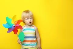 Little boy with rainbow whirligig. Portrait of little boy with rainbow whirligig on yellow background Stock Image